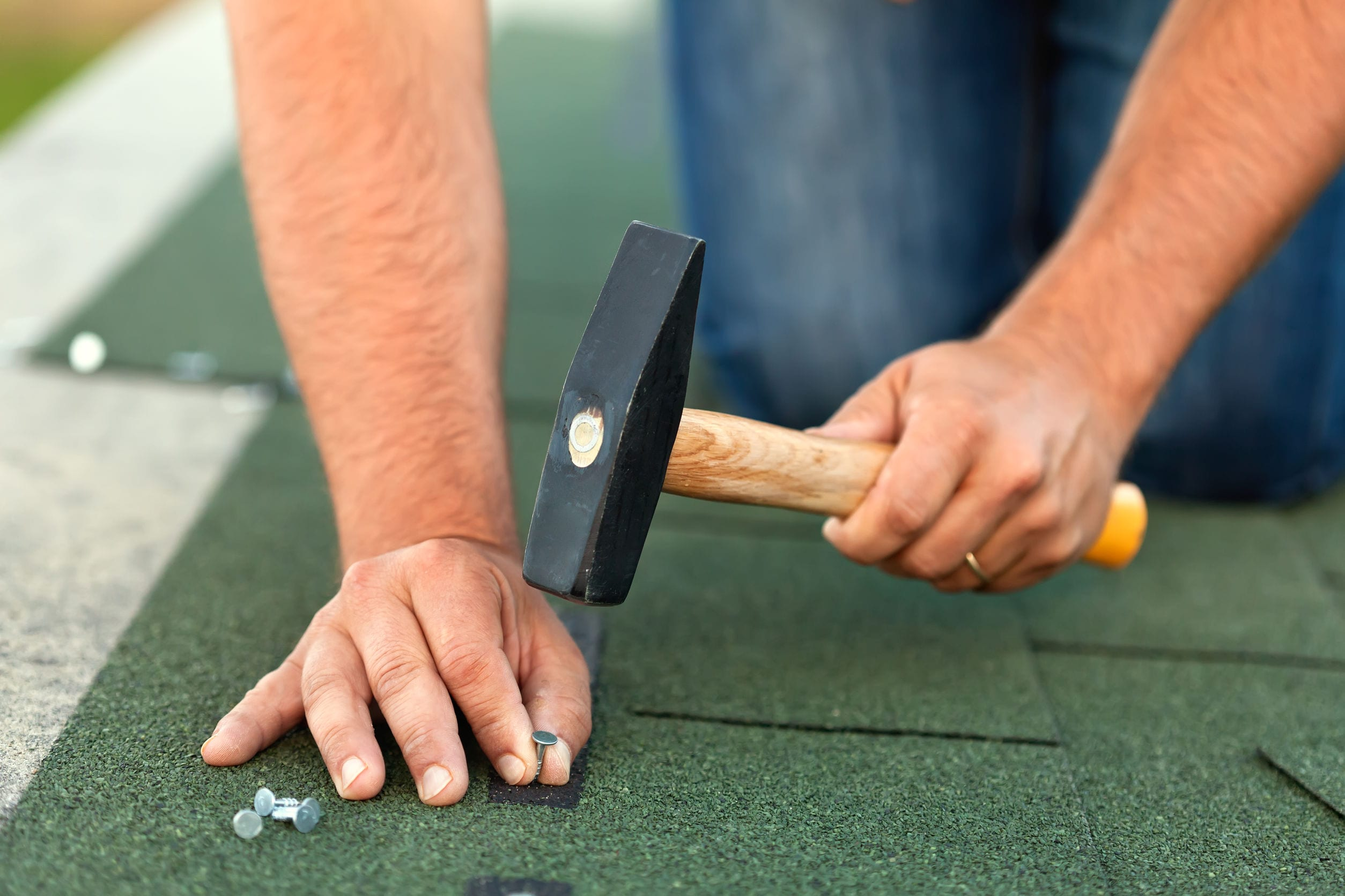 Worker hands installing bitumen roof shingles - fastening one with nails, closeup